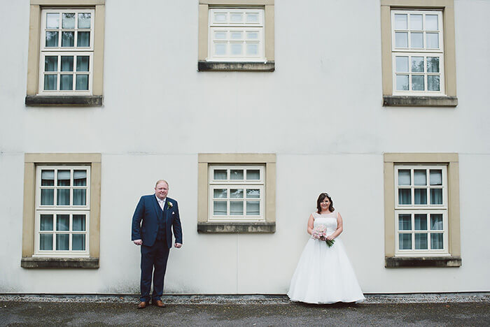 Bride and groom standing in front of a house