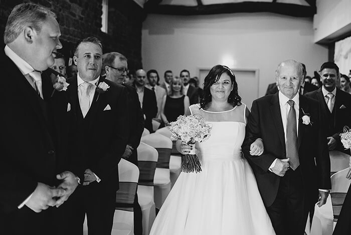 Photograhpy showing a bride and dad walking downth aisle at their wedding