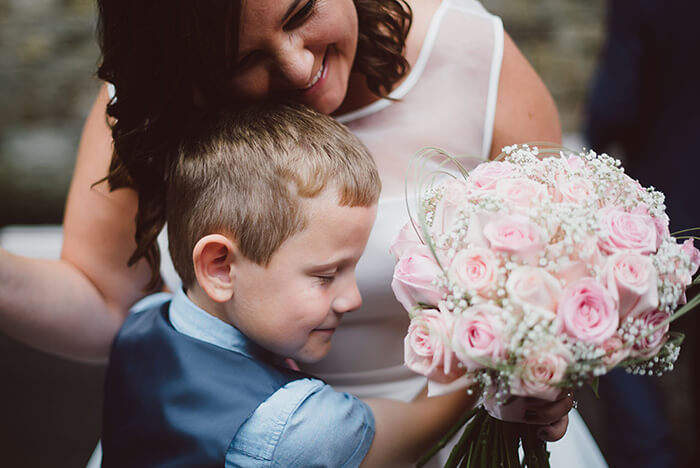 A photograph of a page boy and bride together with a bouquet of flowers