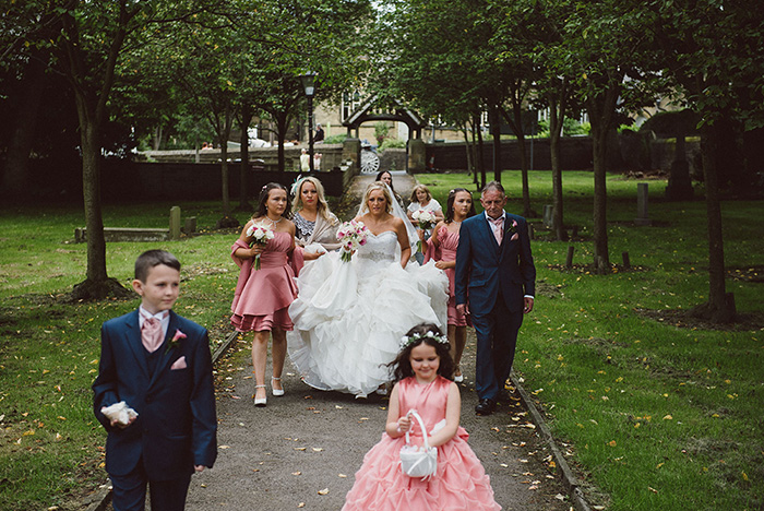A photograph of the bride, bridesmaides, page boys and dad walking towards the church