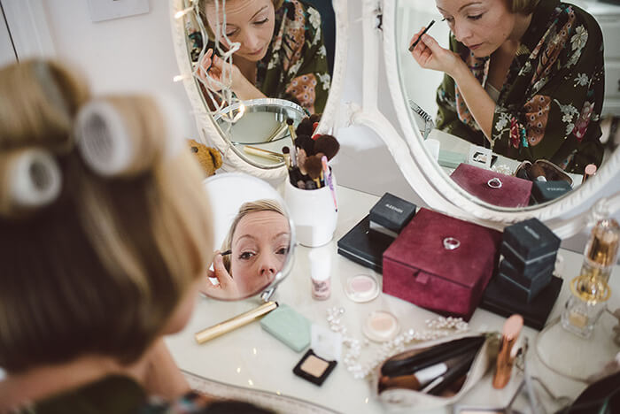 The bride adding makeup on her wedding day.