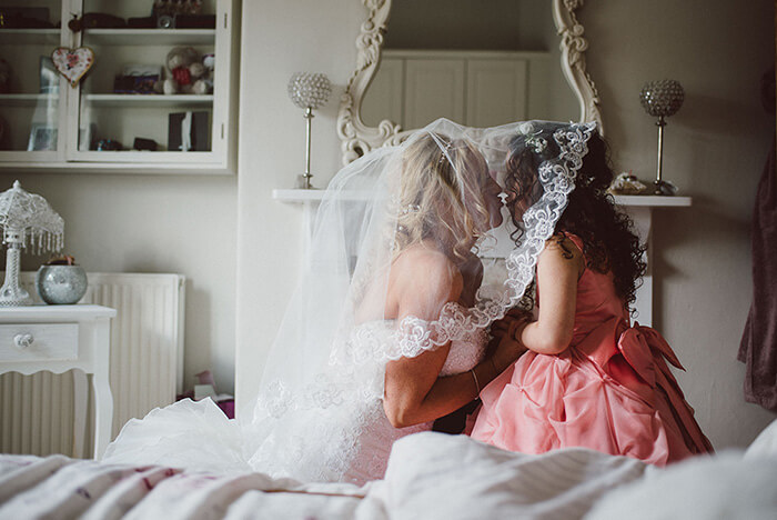 Bride kissing a bridesmaid on the morning of the wedding day