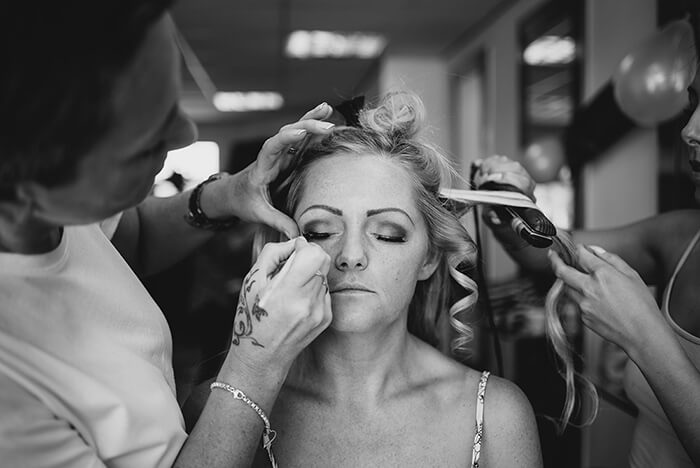 A black and white photograph of the bride having their makeup done